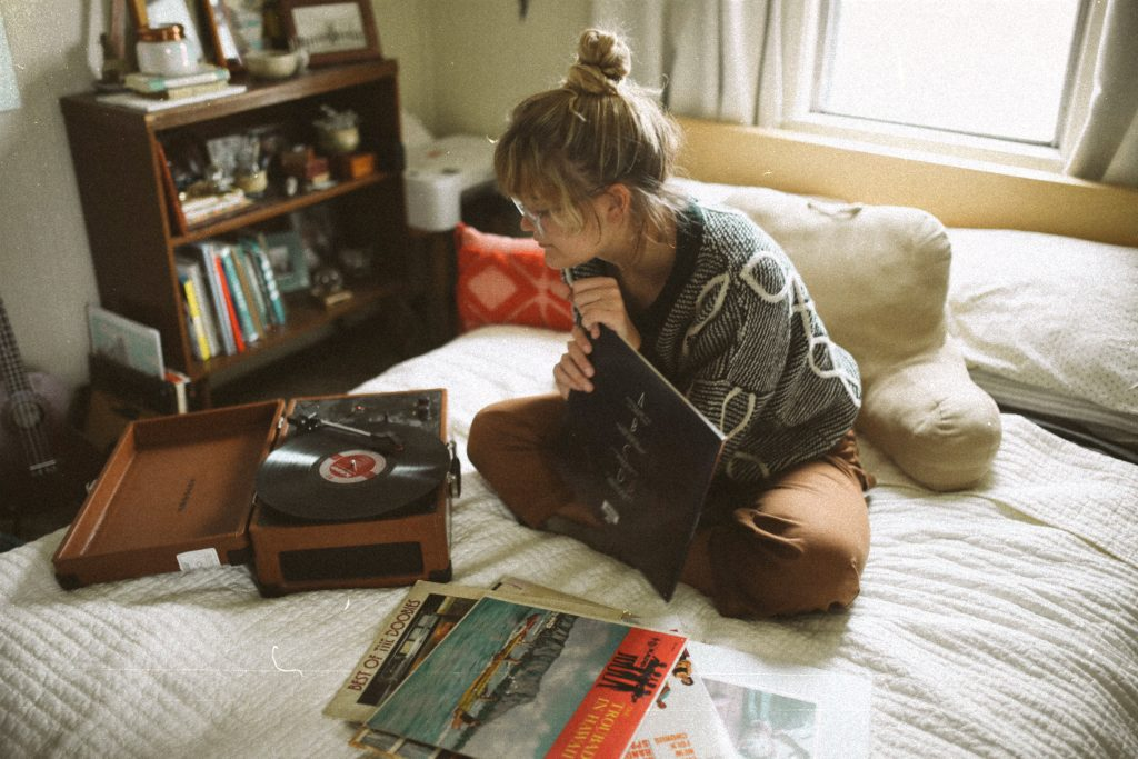 Girl sitting on a bed and listening to music.